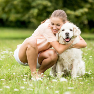 golden retriever and girl hugging and having fun outside dog groomer