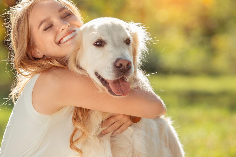 new pet owner hugging large dog