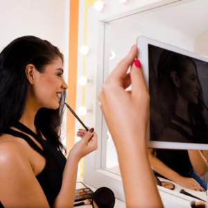 beautiful woman applying makeup while friend films on ipad
