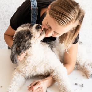 dog groomer cuddling with dog